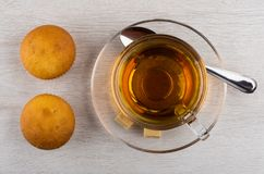 茶杯、多块的糖和茶匙在茶碟,两个松饼 图库摄影