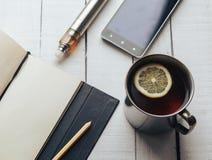 茶杯、手机、笔记本、铅笔和电子香烟vaping的 库存图片