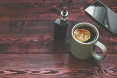 茶杯、手机和电子香烟vaping的在木桌上 免版税库存照片