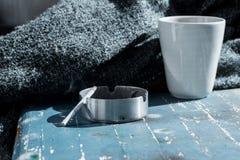 茶杯、毯子和烟灰缸灰色秋天背景 库存照片