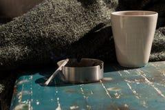 茶杯、毯子和烟灰缸灰色秋天背景 免版税库存照片