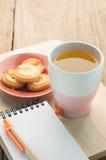 茶杯、点心曲奇饼在木地板上和笔记薄纸 免版税图库摄影