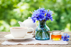 茶杯、茶壶、蜂蜜瓶子和矢车菊夏天花束  免版税库存照片