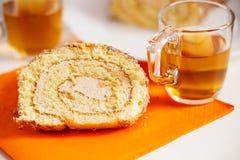 茶杯和切片甜奶油色卷 免版税库存照片