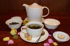 茶杯和茶壶有瓣和蜡烛的静物画 库存照片
