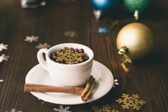 茶杯用一根肉桂条在一张木桌上在圣诞节装饰中 图库摄影