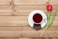 茶杯,郁金香花,巧克力 木的表 顶视图 复制s 免版税库存图片