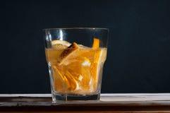茶点与橙色鸡尾酒的戒毒所水与气泡和在一个混凝土墙的黑背景的飞溅 库存照片