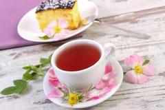 茶用乳酪蛋糕和狂放的玫瑰色花在老木背景 免版税库存图片