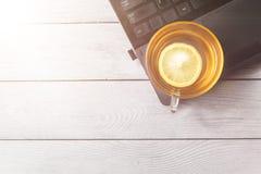茶用在膝上型计算机的柠檬和白色木背景,茶时间的概念,放松与拷贝空间,顶视图,平展 库存照片