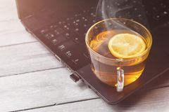 茶用在膝上型计算机的柠檬和白色木背景,茶时间的概念,放松与拷贝空间 免版税图库摄影
