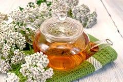 茶用在玻璃茶壶的欧蓍草在餐巾 库存图片