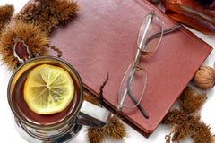 ?? 茶用柠檬、闭合的书籍、玻璃和栗子 图库摄影