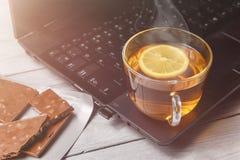 茶用柠檬和巧克力在膝上型计算机和白色木背景,茶时间的概念,放松 库存照片