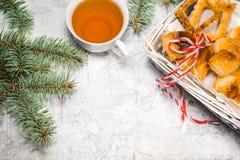 茶用gingebread曲奇饼在圣诞节晚上 在白色木背景顶视图copyspace的云杉的分支附近杯 免版税库存图片