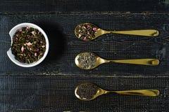 茶的三种类型在绿色的匙子-,黑色和Rooibos的 免版税库存图片