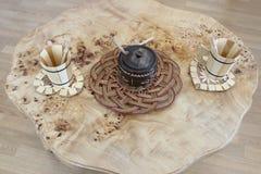 茶的木桌与木立场、木糖罐和木杯子 免版税库存图片