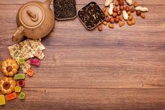 茶的构成木表面上的 从黏土的棕色茶壶与驱散茶、杏仁和榛子 绿色,黑色 库存照片