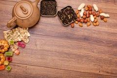 茶的构成木表面上的 从黏土的棕色茶壶与驱散茶、杏仁和榛子 绿色,黑色 免版税图库摄影