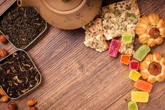 茶的构成木表面上的 从黏土的棕色茶壶与驱散茶、杏仁和榛子 绿色,黑色 免版税库存照片