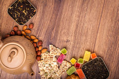 茶的构成木表面上的 从黏土的棕色茶壶与驱散茶、杏仁和榛子 绿色,黑色 免版税库存图片