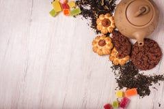 茶的构成木表面上的 从黏土的棕色茶壶与驱散茶、杏仁和榛子 绿色,黑色 图库摄影