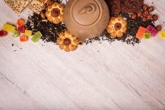 茶的构成木表面上的 从黏土的棕色茶壶与驱散茶、杏仁和榛子 绿色,黑色 库存图片