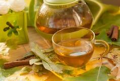 茶罐、一个杯子新鲜的茶,秋叶和花 免版税库存图片