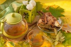 茶罐、一个苹果自创饼的片断在板材的,一个杯子新鲜的茶和秋叶和花 库存图片