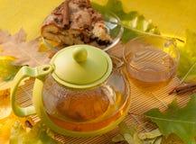 茶罐、一个苹果自创饼的片断在板材的,一个杯子新鲜的茶和秋叶 库存图片