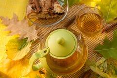 茶罐、一个苹果自创饼的片断在板材的,一个杯子新鲜的茶和秋叶 库存照片