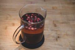 茶罐用在木背景的莓果 库存图片