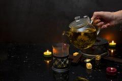 茶罐,蜡烛,shockolate,奶蛋烘饼,黑暗的背景 免版税库存图片