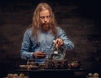 茶道概念 一个红头发人行家男性的画象与长的头发和充分的胡子的在一件蓝色衬衣穿戴了 免版税库存照片