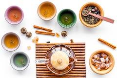 茶道概念 在竹席子,杯子,干茶叶,在白色背景顶视图的糖的茶罐 库存照片