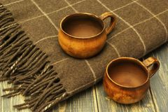 茶陶瓷古色古香的杯子和软的温暖的羊毛格子花呢披肩在黑暗的木背景 免版税库存图片