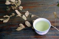 茶顶视图在杯子的有干燥分支和叶子的,在木桌上的浅褐色的颜色 库存照片