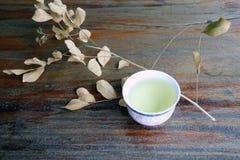 茶顶视图在杯子的有干燥分支和叶子的,在木桌上的浅褐色的颜色 免版税图库摄影