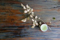 茶顶视图在杯子的有干燥分支和叶子的,在木桌上的浅褐色的颜色 免版税库存图片