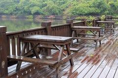 茶馆湖边木大阳台在雨中 库存照片