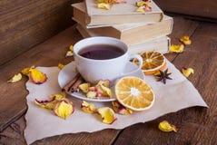 茶,书,烘干了在木背景的玫瑰花瓣 免版税库存图片