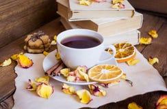 茶,书,烘干了在木背景的玫瑰花瓣 免版税库存照片