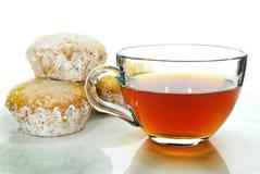 茶,在白色背景隔绝的搽粉的糖的松饼。 免版税库存照片