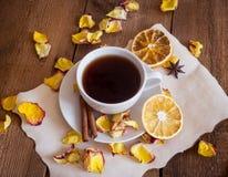 茶,干桔子,在木背景的干玫瑰花瓣 免版税库存图片