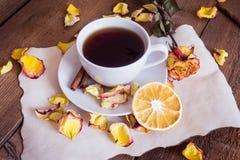 茶,干桔子,在木背景的干玫瑰花瓣 免版税库存照片