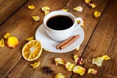 茶,干桔子,在木背景的干黄色玫瑰花瓣 库存图片