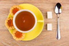 茶,曲奇饼用在茶碟,多块的糖的果酱 库存图片