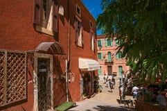 茶黄的传统五颜六色的房子和人们在鲁西永 免版税库存照片