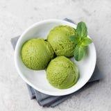 绿茶matcha在白色碗的冰淇凌瓢在一张灰色石背景拷贝空间顶视图 免版税库存图片