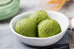 绿茶matcha在白色碗的冰淇凌瓢在灰色石背景 免版税库存图片